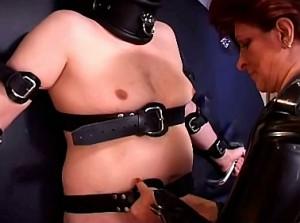 Meedogenloze domina bind haar slaaf aan het wiel